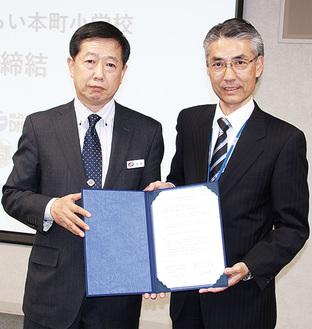 協定書を持つ内田社長(左)と小正校長(右)