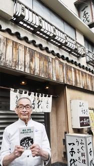 時代劇のセットのような風情ある「一千代」の前で、本を手に福田さん。店内には懐かしい大道芝居のポスターが飾られている