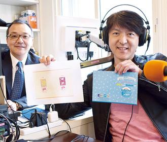 記念小型印の図案とオリジナル切手台紙を手にするパーソナリティーの新井昌和さん(右)。左はマリンFMの笹原代表