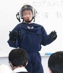 防護衣を着てトークライブを行う古澤さん(桜木町のクラーク記念国際高校で)