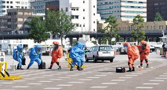テロに使用された化学物質特定に連携する警察(青色)と消防の隊員