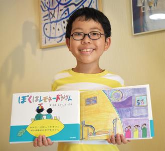 絵本を手にす榮島四郎さん