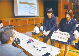 新商品案の見本を審査員に見せる生徒