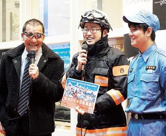 消防団員と語る蝶野さん(左)
