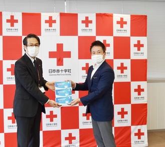 マスクを寄贈する花本社長(右)
