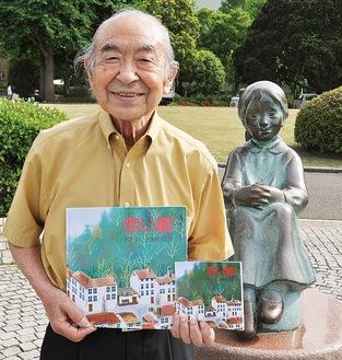 山下公園の「赤い靴はいてた女の子像」の前で絵本を手にする松永さん(右が復刻版で左はオリジナル本)