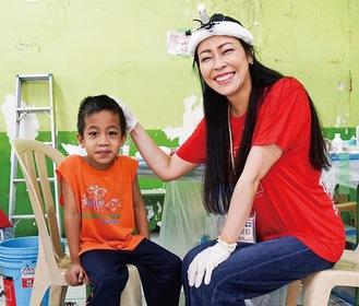 スラム街で診察を受け笑顔の少年と木村医師(右)