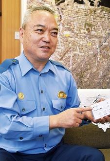 迷惑電話防止機器を手に説明する伊勢佐木警察署の川瀨 伸二署長