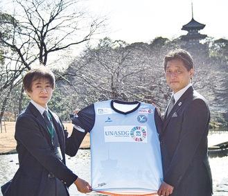 三溪園でユニフォームを持つ吉野社長(右)と吉川事業課長