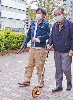 現地調査の様子を再現する市川さん(左)