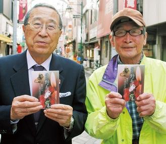 野毛の街で本を手にする平出さん(左)と福田さん。表紙画は野毛大道芸でおなじみの森直実さんが描いた