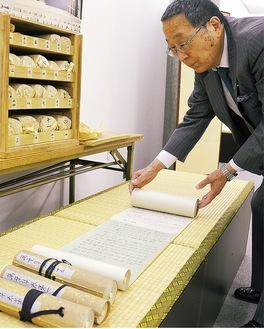 万葉集を広げて見せるゴールデン文具の平出会長