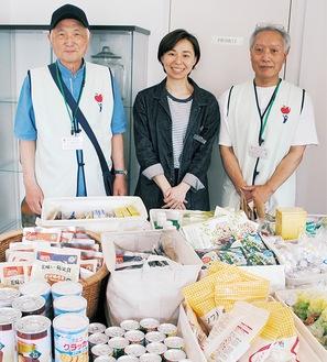 テーブルの上に並んだ提供品の前で、左から加藤理事長、小村さん、宮原事務局長