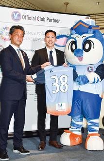 背番号「38」のユニフォームを手にするアオチョン選手(中央)。左は吉野代表取締役。右はクラブマスコットのハマピィ