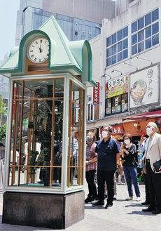 関係者が見守るなか新たな時を刻み出した「からくり人形時計」。場所は中区伊勢佐木町2丁目の「シマミネ」近く(午前10時から午後9時の毎正時と30分に3分間稼働)