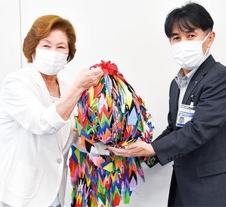 千羽鶴を贈る塩島副会長(左)