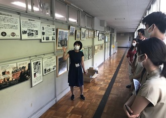 職員室前に貼られたパネルの前で、キリンビールと北方小にまつわる歴史を説明する今野校長