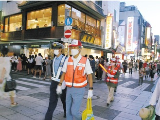 にぎわう中華街をパトロールする参加者たち=7月23日