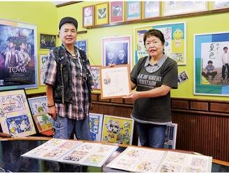オーナーの平野いづみさん(右)が描いたゆずのイラストや貴重なサインが飾られた店内。兄の正さん(左)と共にゆずっこを迎える