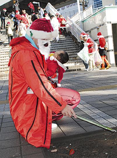 サンタ姿で街を清掃