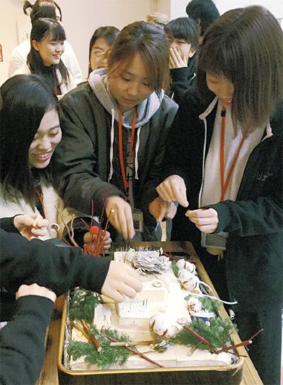 冬らしい装飾を施された豆腐に針を刺していく学生たち。豆腐は23丁分が使用された
