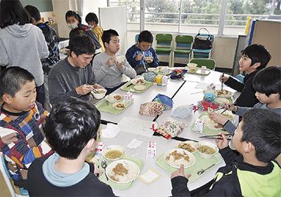 野菜づくりを教わった加藤さんを囲んで給食を食べる児童たち。おかわりする児童が続出し、スープの容器はすぐに空っぽに。「国際交流を『食べる』ということで体感できたのもよかった」と加藤さん=3月7日、同校ランチルームで