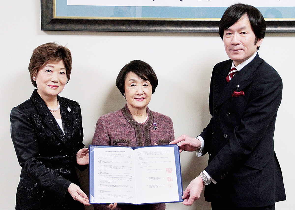 協定書を持つ都築理事長(左)、市長、寺師会長