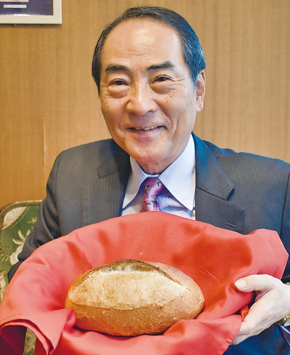 同社の代表商品「チーズバタール」を手にする三藤社長