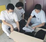 集まった衣服を仕分ける吉永さん(右)ら