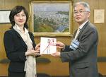 東京ガスの早川支社長(左)から山口区長に目録が渡された