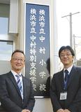 両校の名前が入った1枚の校名板(右が中村小の中川校長、左が中村特別支援学校の佐塚校長)