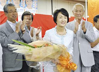 事務所内で関係者からの花束を手に謝意を述べる林氏