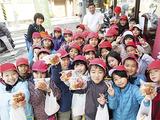 日枝丸パンを手に笑顔の3年3組の児童たち
