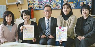 本を手にする青木会長(右から2人目)ら保護者(中央は佐塚校長)