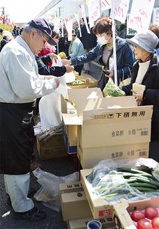 野菜・果物の模擬店に集まる人々