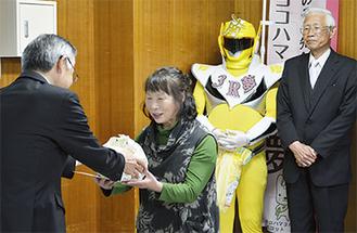 山口区長から記念品を受け取る六ツ川地区連合自治会の関係者