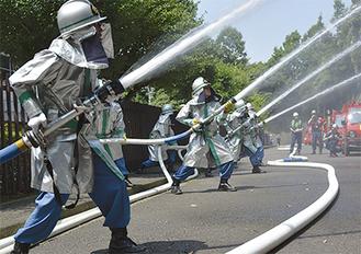 一斉放水する消防団員ら