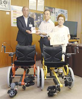 桐谷次郎県教育長(左)に目録を渡す千葉昭夫さんと圭子さん