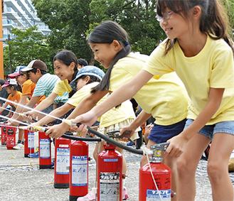 消火器を使って放水する児童