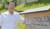 「リラのいえ」の前で笑顔を見せる田川さん