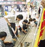 弘明寺商店街を清掃する生徒(写真提供・同校)