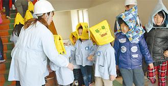 避難訓練で階段を上る児童と園児