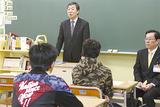 設置された本を横にし、生徒へ語りかける木村校長(右は中島区長)