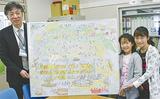 昨秋完成したサステイナブルマップを持つ住田校長(左)と6年生