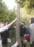 空襲の傷跡が残る中村八幡宮の石碑を見学するY校生(写真提供・横浜商業高校)