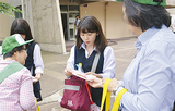 高校生に防犯ブザーを渡す蒔田生活安全母の会の女性