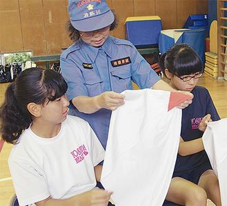 消防団員から三角巾の使い方を習う生徒