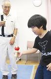 大人が見守る中、けん玉に挑戦する小学生
