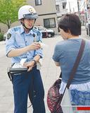 自転車の運転者に注意を促す警察官
