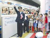 最初の快速電車の出発を合図する石坂寿邦駅長